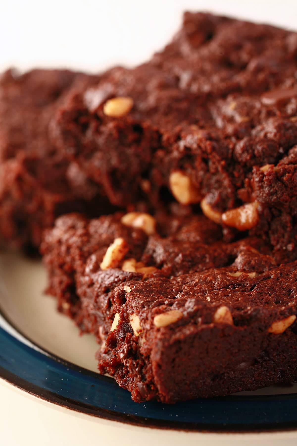 A small plate, piled with 4 double chocolate walnut brownies.