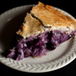 A slice of a creamy blueberry amaretto pie, on a small white plate.