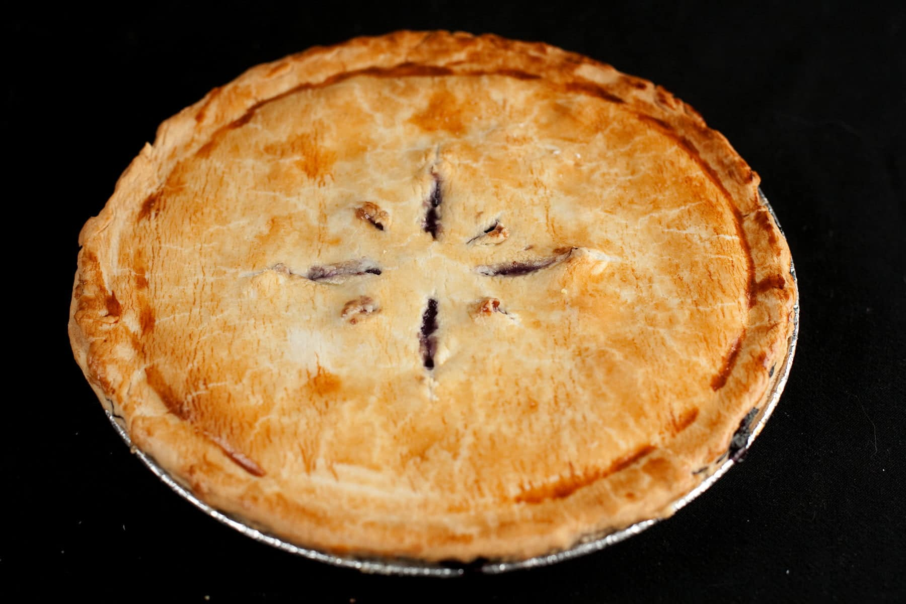 A whole 2-crust pie, against a black background. Slits cut into the top crust reveal it to be a blueberry pie.