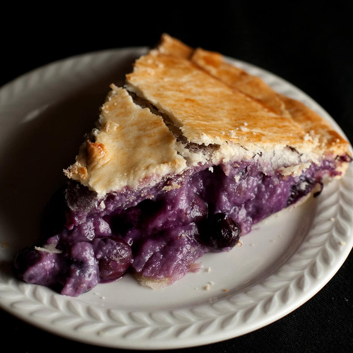 A slice of a creamy looking blueberry pie, on a small white plate.