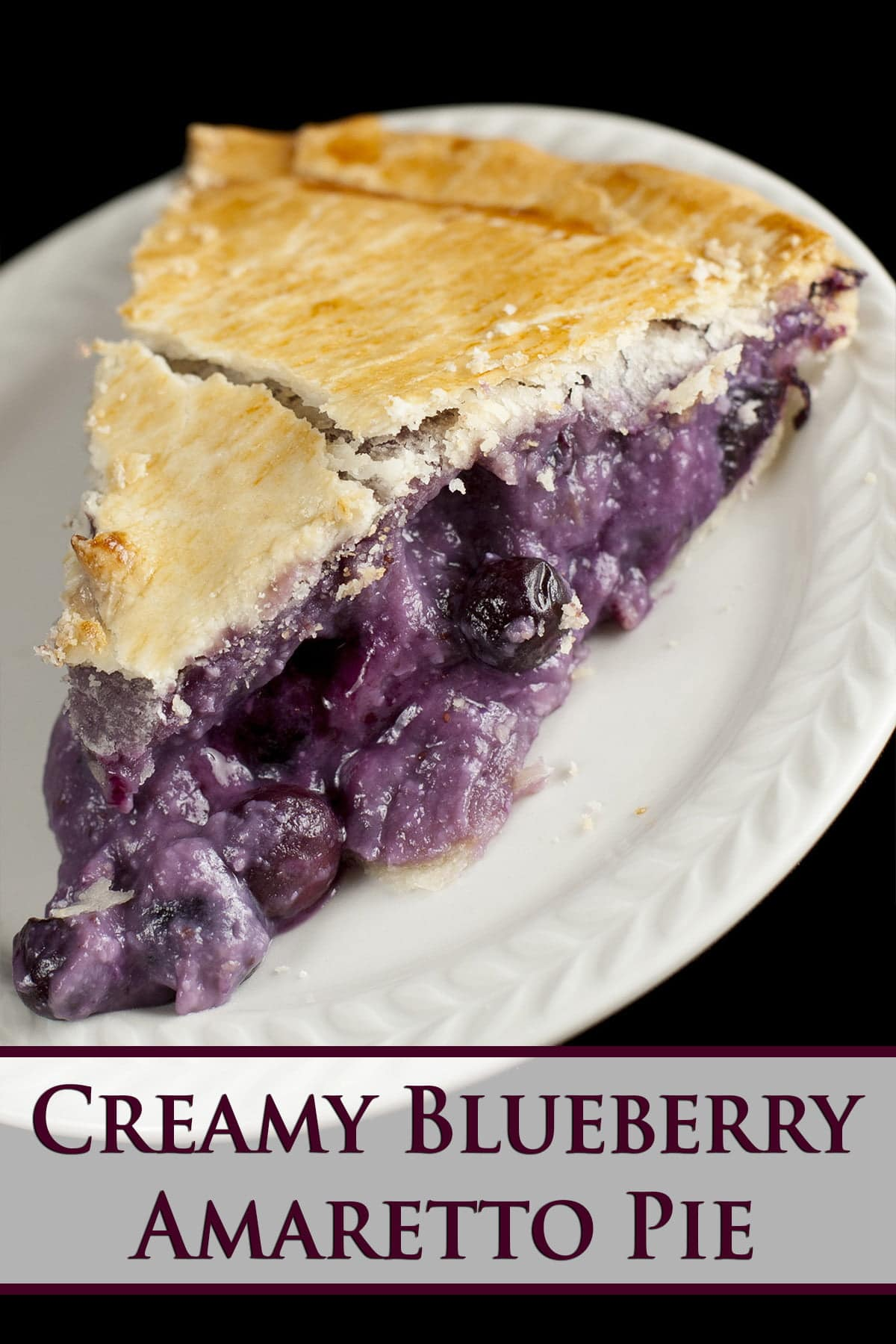 A slice of a creamy looking blueberry pie, on a small white plate. Purple text overlay says creamy blueberry amaretto pie.