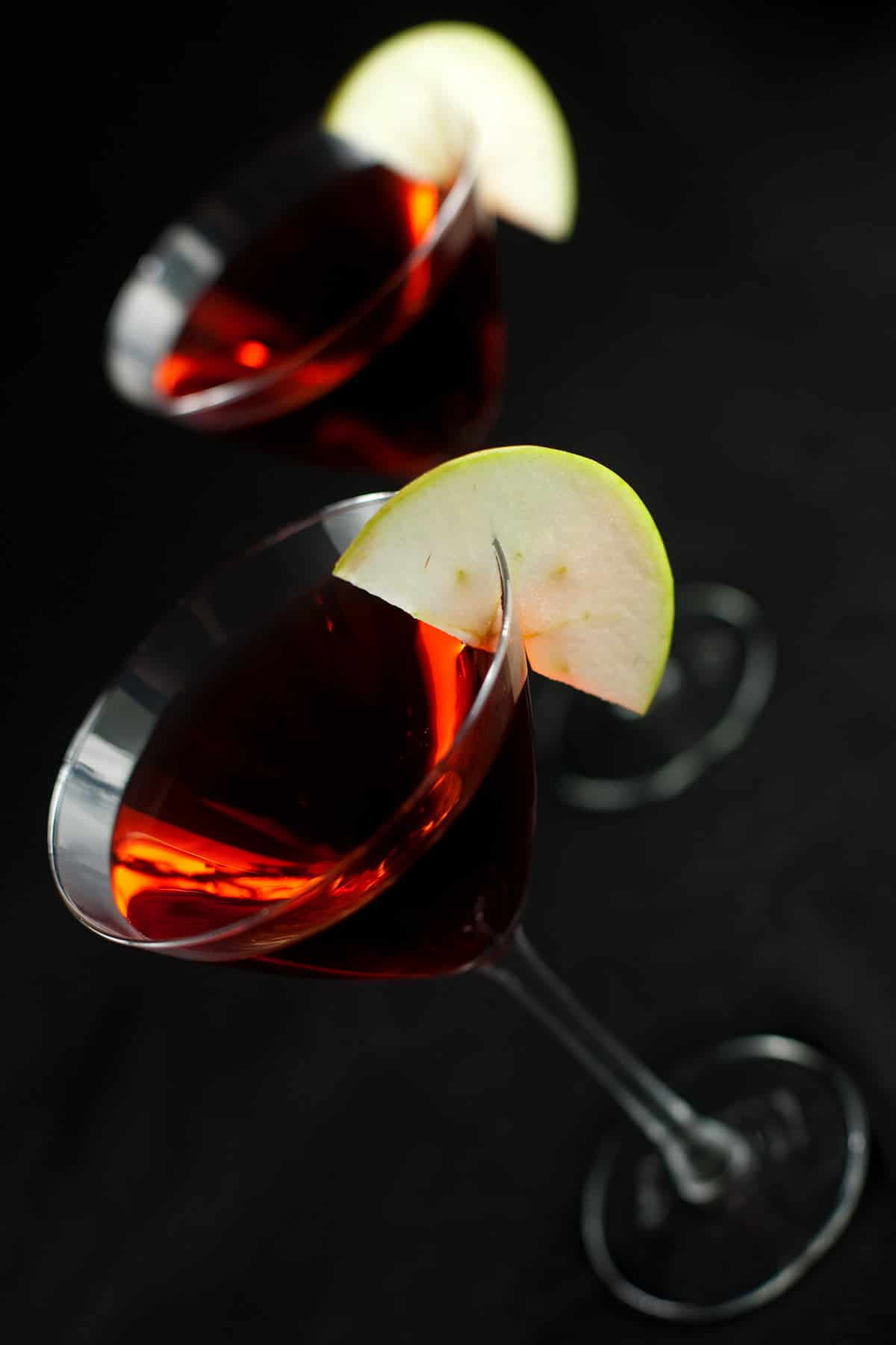 Two Candy Apple Martinis - large martini glasses are filled with a red liquid, and garnished with apple slices.
