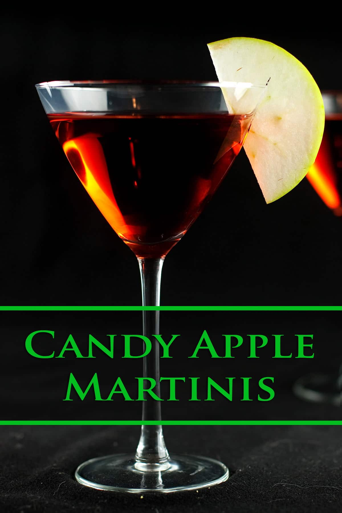 Two large martini glasses are filled with a red liquid, and garnished with apple slices.