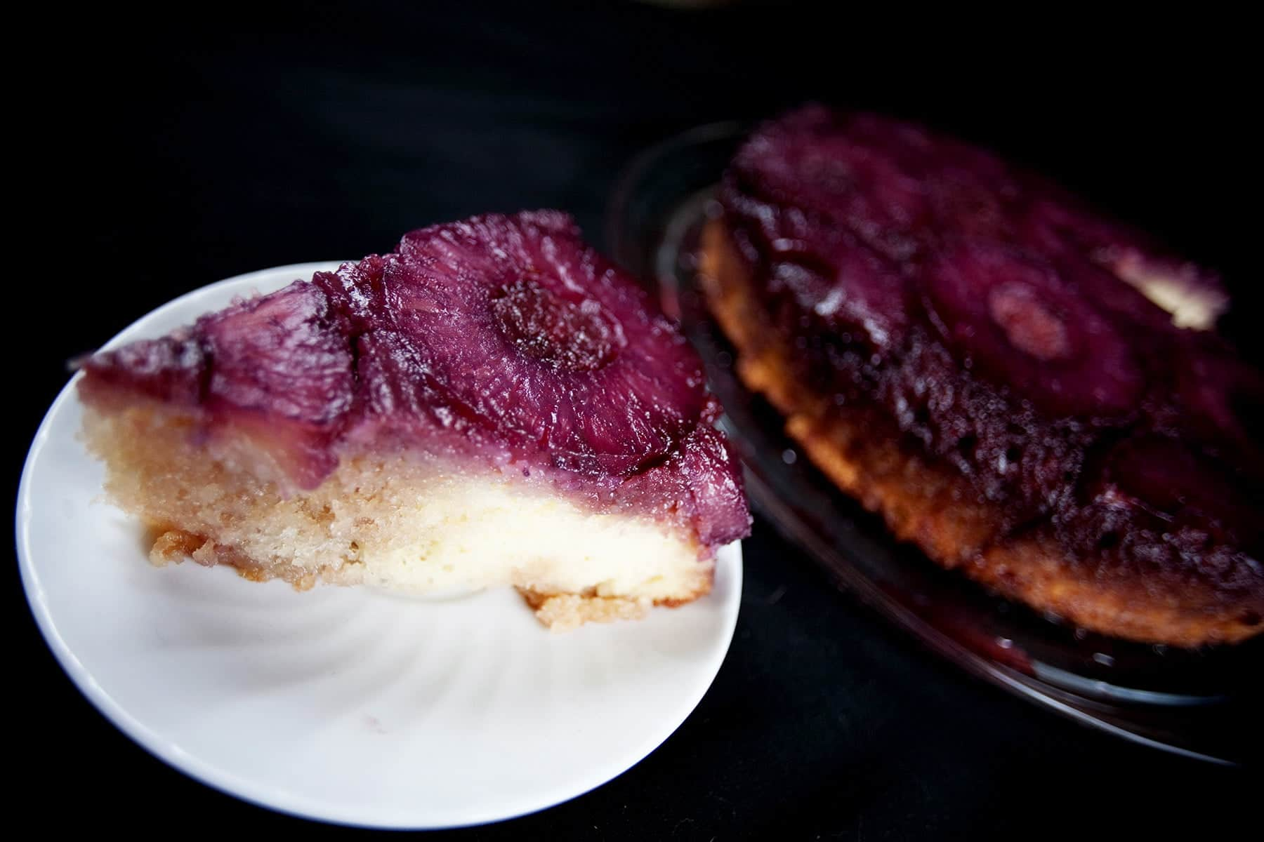 French Martini Upside Down Cake - A round pineapple upside down cake, with a VERY purple top! A slice has been cut out and is on a plate next to the main cake.