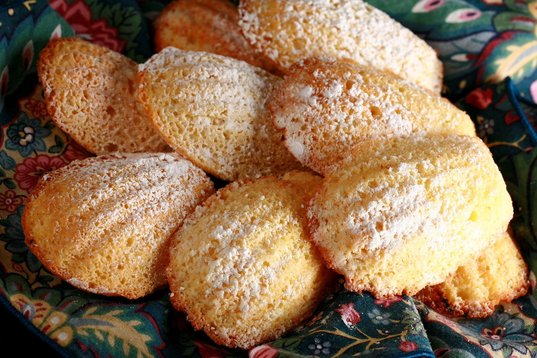 A small pile of sugar dusted Limoncello Madeleines, on a napkin lined plate.