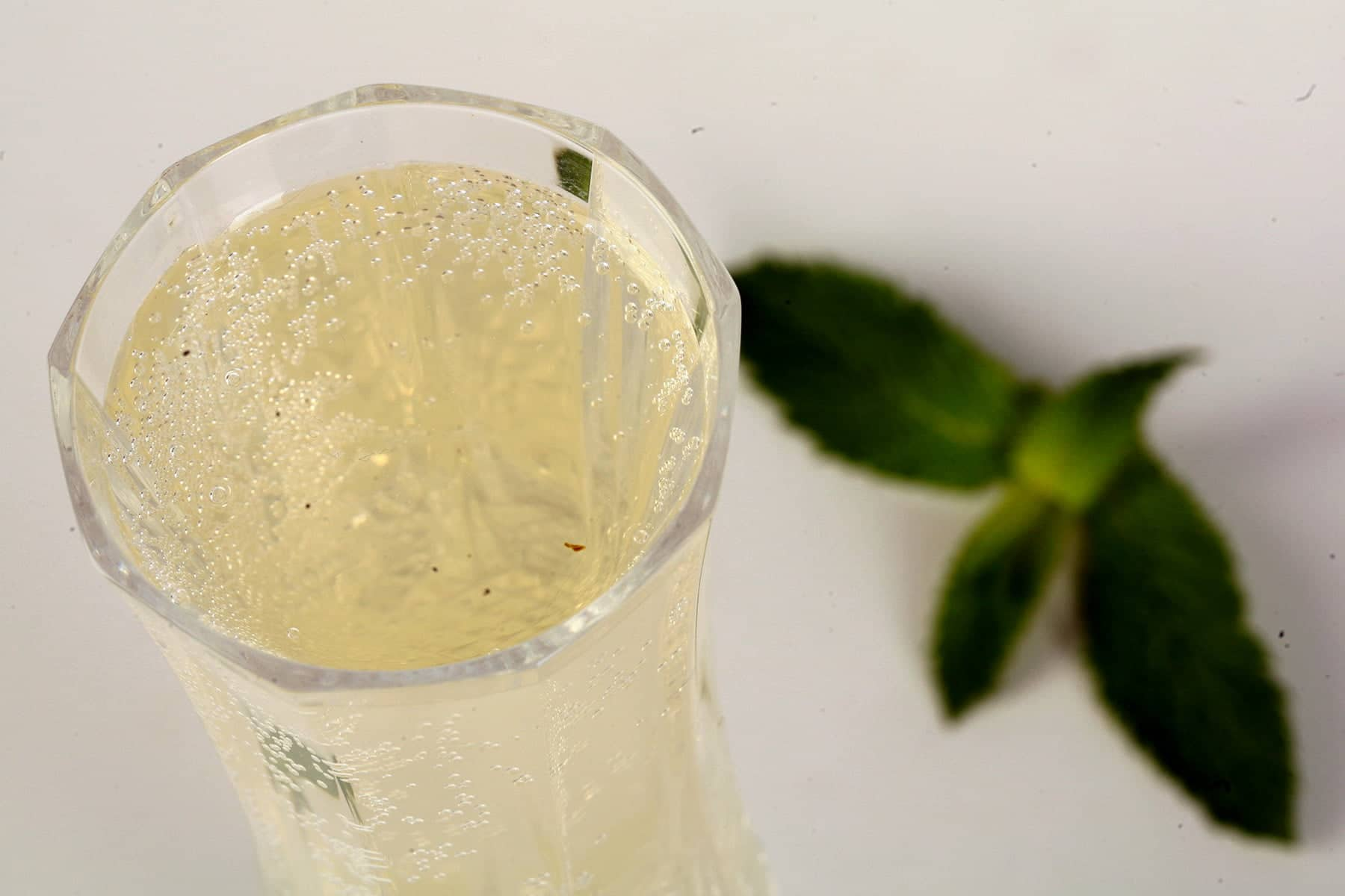 A tall champagne flute of sparkling mint wine, with a large spring of mint at the base of the glass. White background.