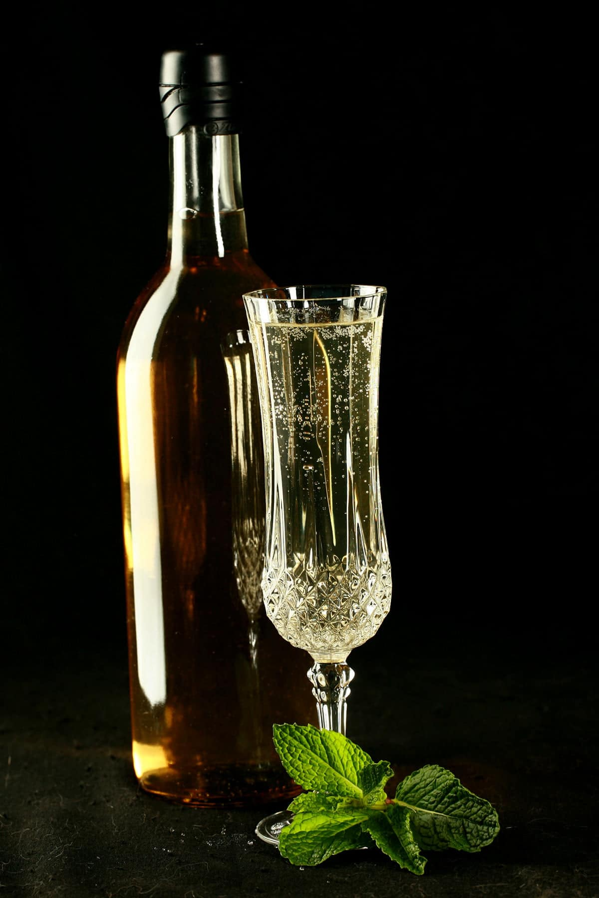 A full wine bottle and a glass of mint wine. There is a spring of mint at the base of the glass, everything is against a black background.