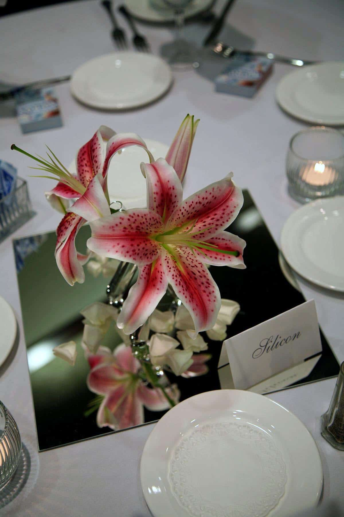 2 stargazer lilies and a bud, in a tripod vase made from test tubes.  The arrangement rests on a large square mirror tile.