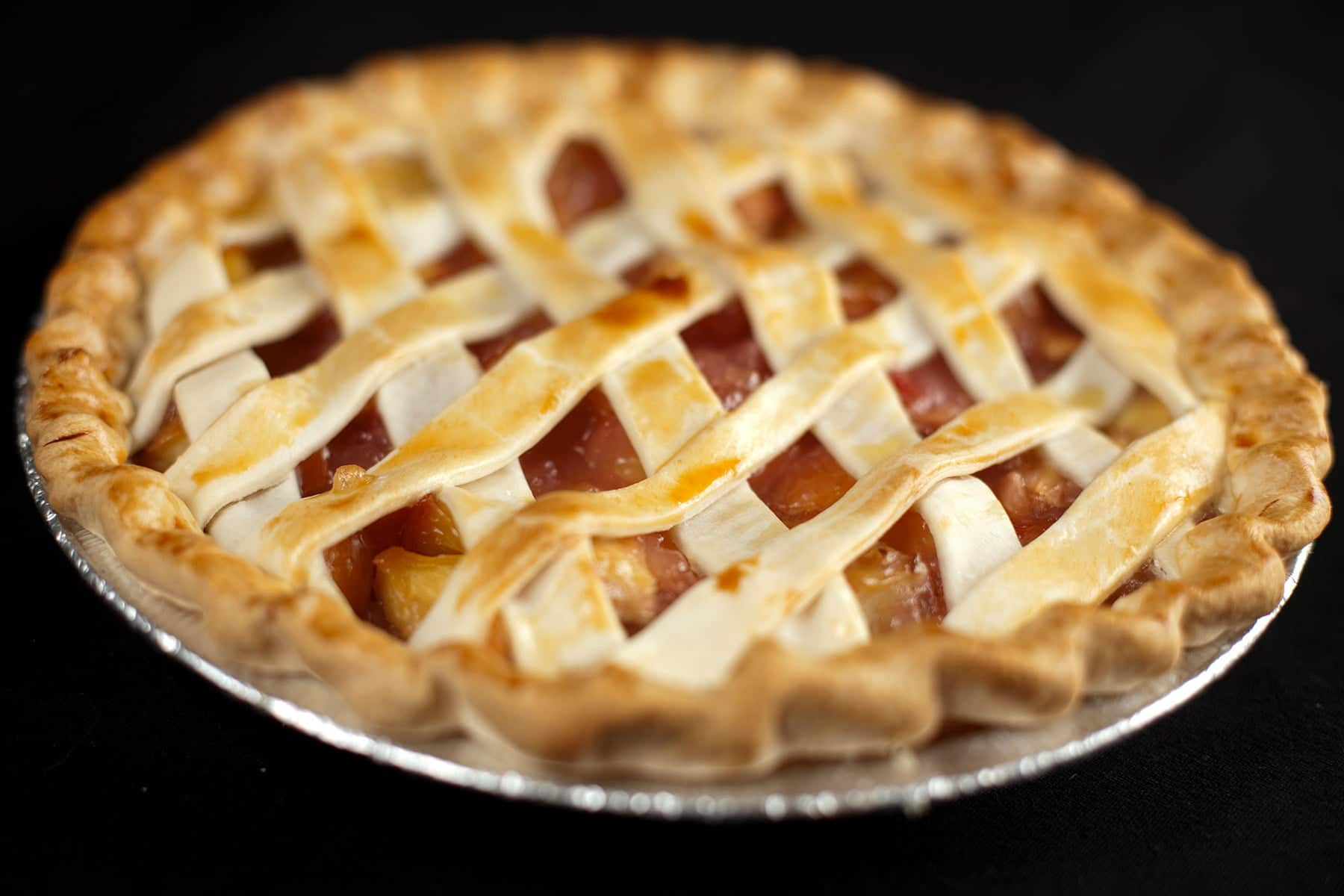 A peach pie with lattice style crust is shown against a black background.