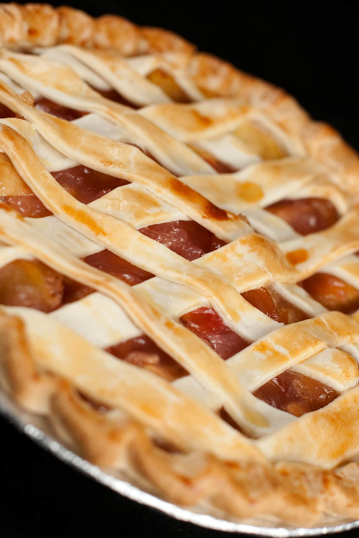 A Southern Comfort peach pie with lattice style crust is shown against a black background.