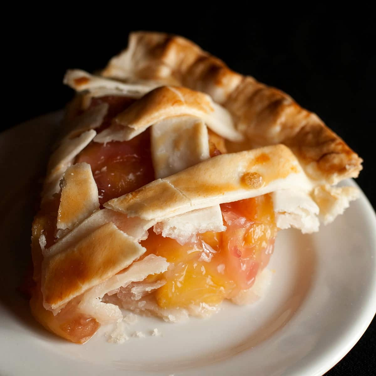 A close up view of a slice of southern comfort peach pie, on a white plate.