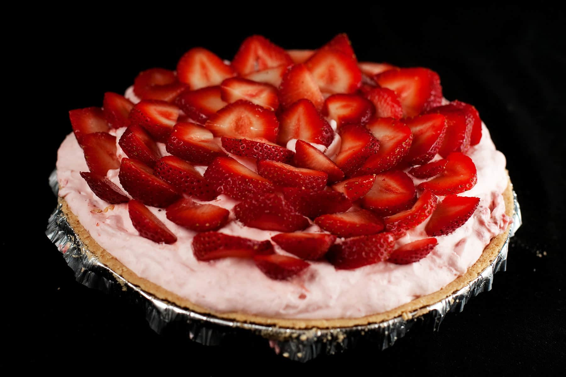 A pink coloured chiffon pie, covered with strawberries.