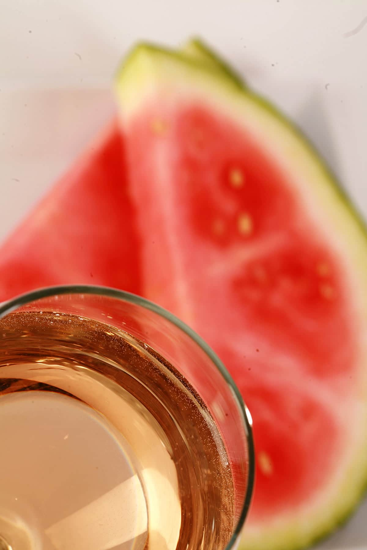 A glass of pale pink wine, next to a white plate with watermelon slices on it.