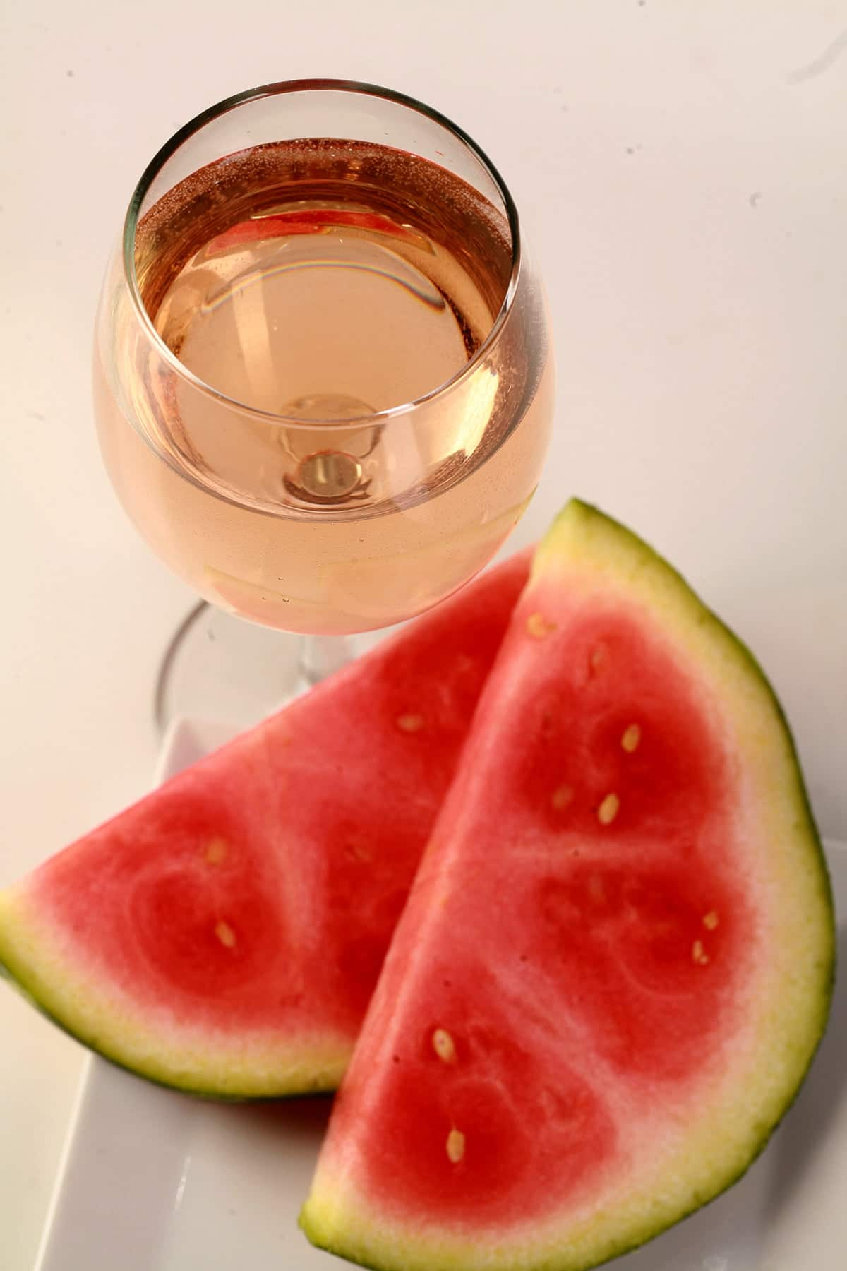 A glass of pale pink watermelon wine, next to a white plate with watermelon slices on it.