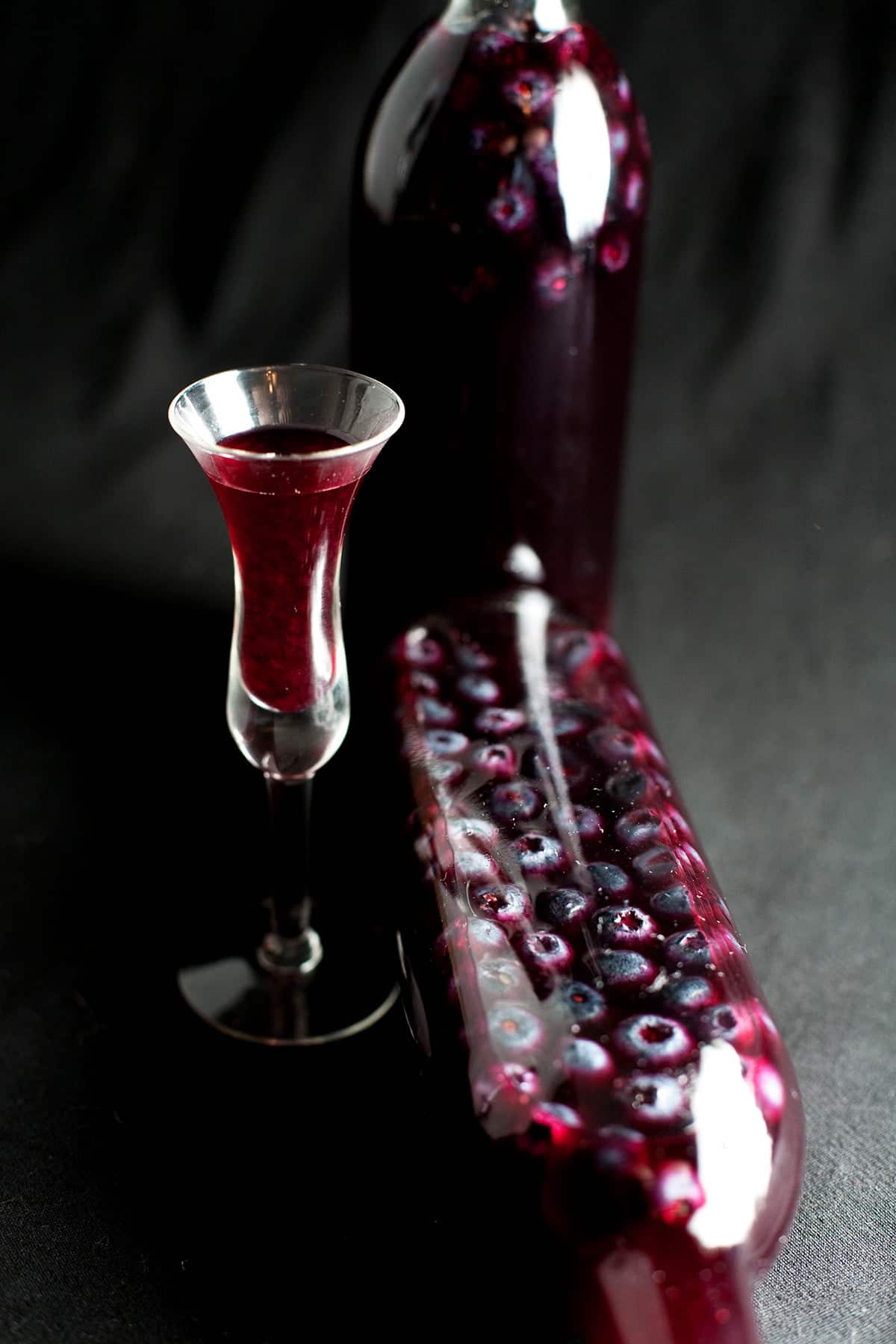 Two bottles of blueberry liqueur - with blueberries showing in the bottles - are shown next to a fluted shot glass filled with the liqueur.