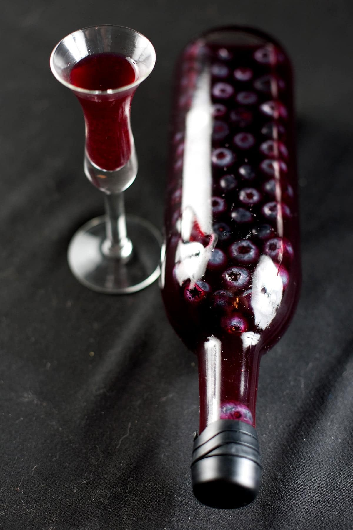 A wine bottled filled with dark purple liqueur and floating blueberries is pictured next to a fluted shot glass filled with the dark purple liquid.