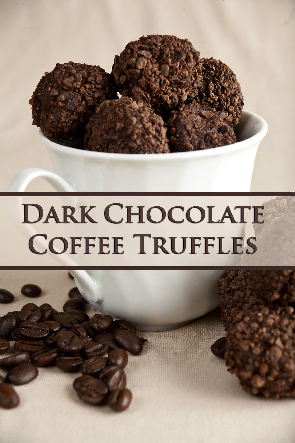 Dark chocolate truffles - coated in smashed coffee beans - fill a white coffee mug. There are stray dark chocolate coffee truffles and coffee beans at the base of the mug.