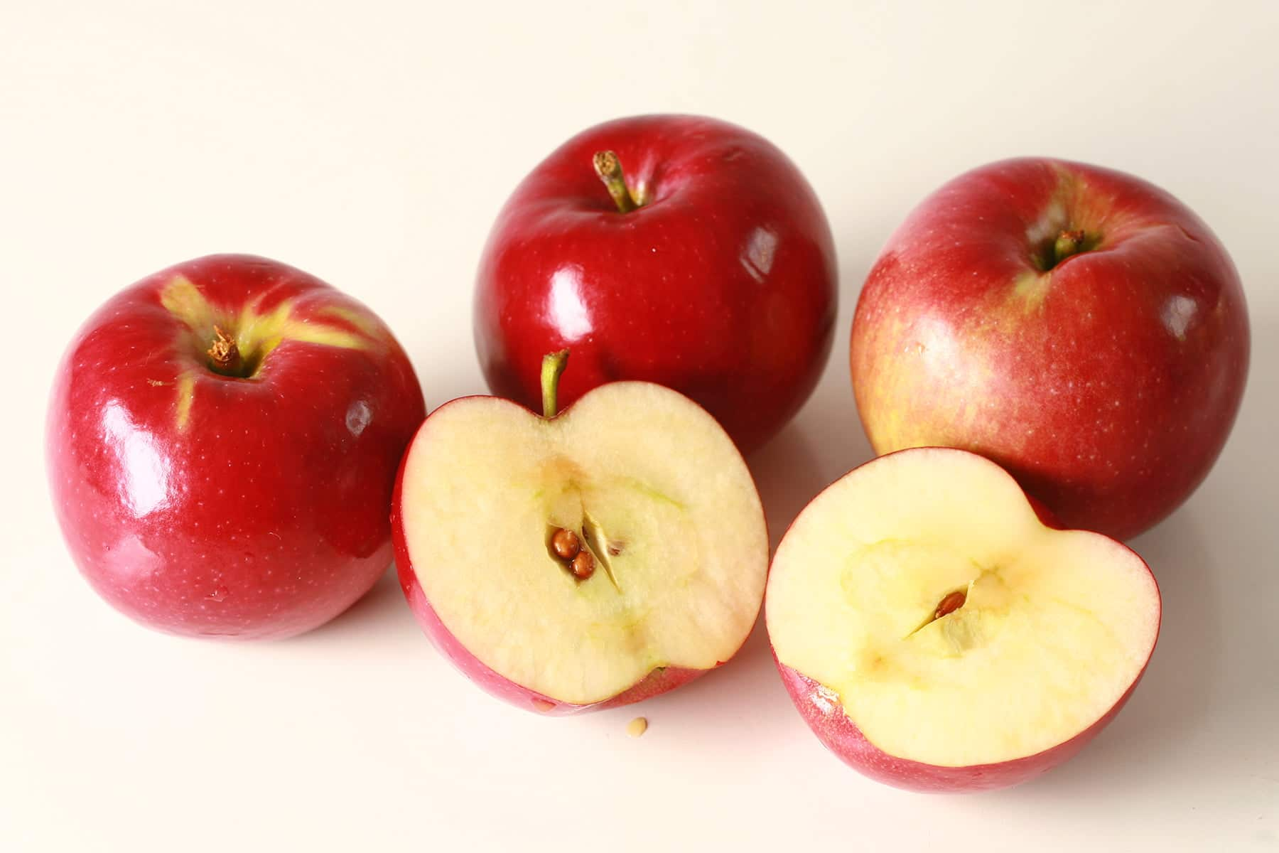 3 whole red apples and 1 apple cut in half, against a white background.