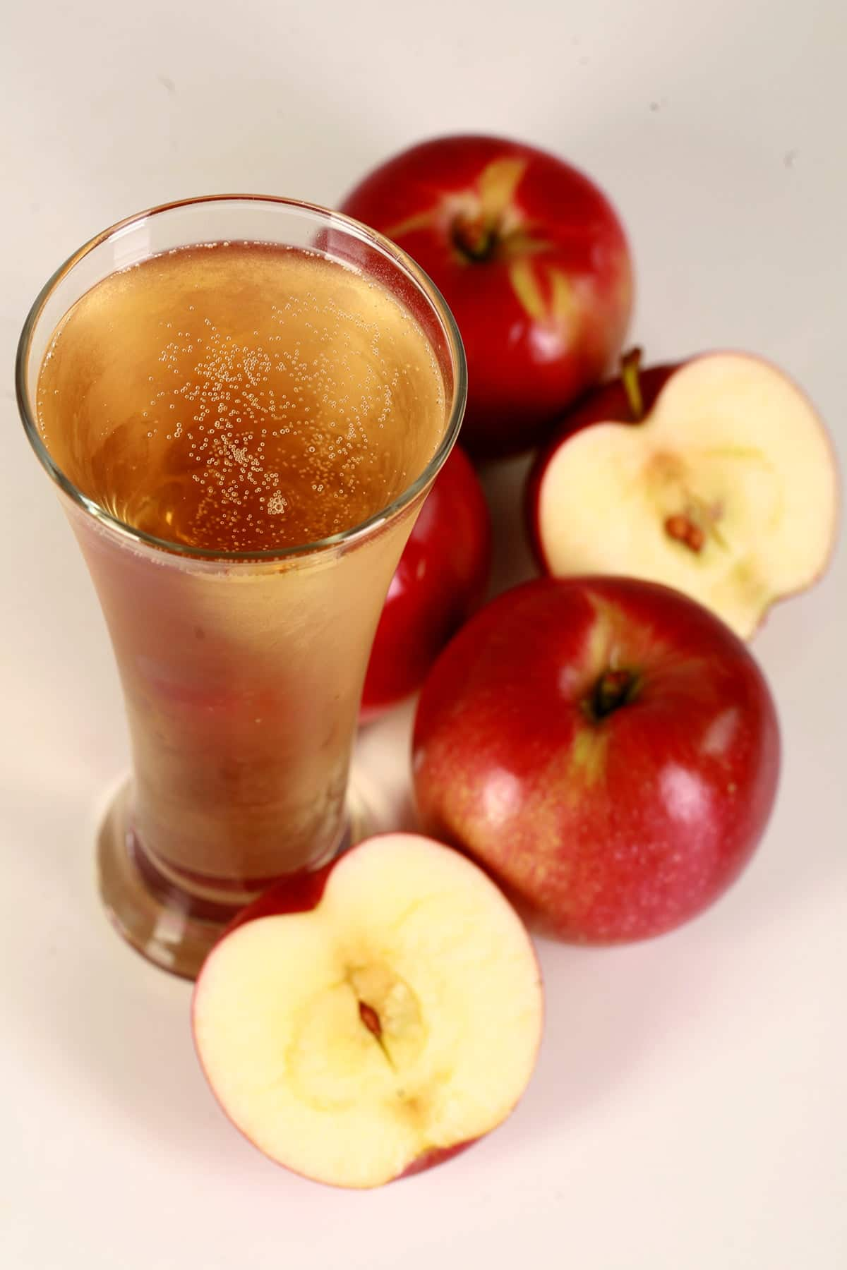 A glass of hard apple cider, surrounded by apples.