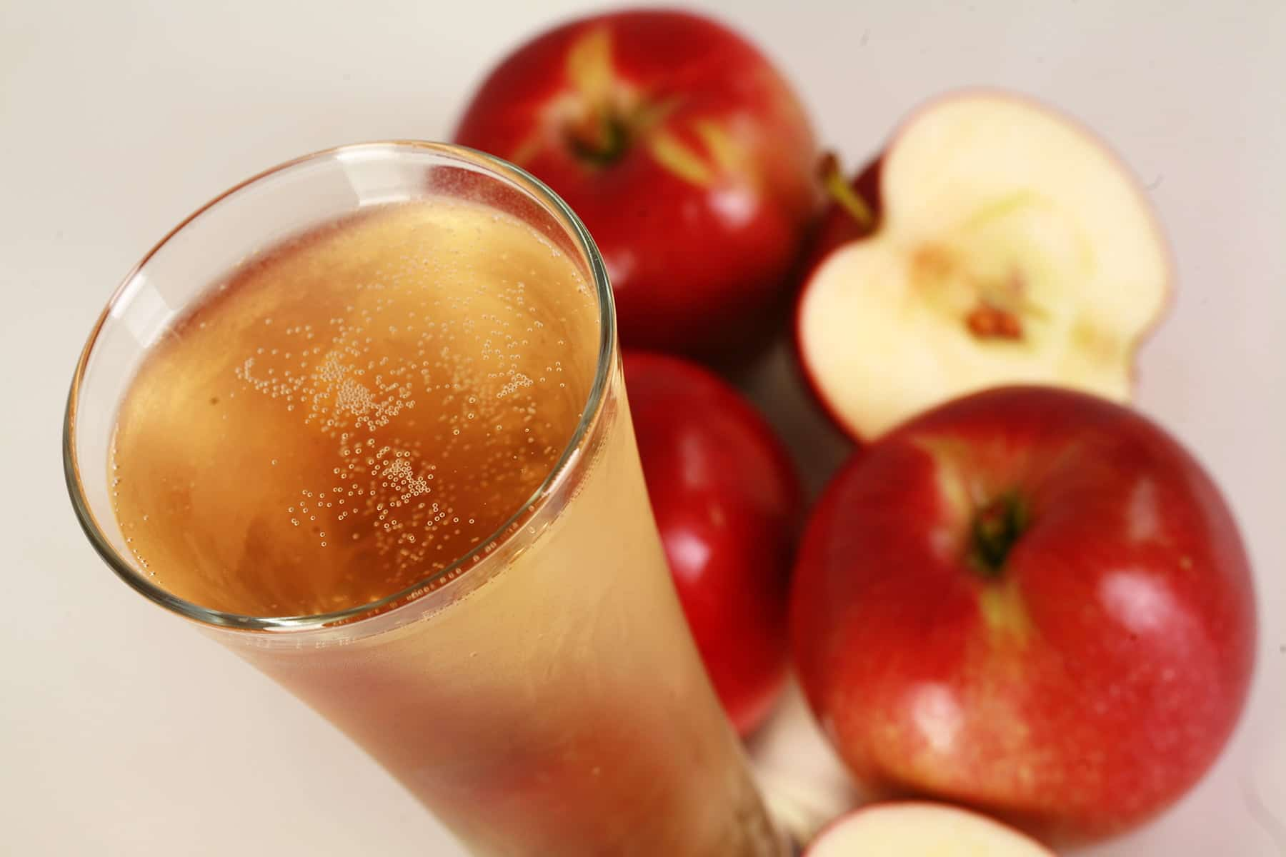 A glass of homemade hard apple cider, surrounded by apples.