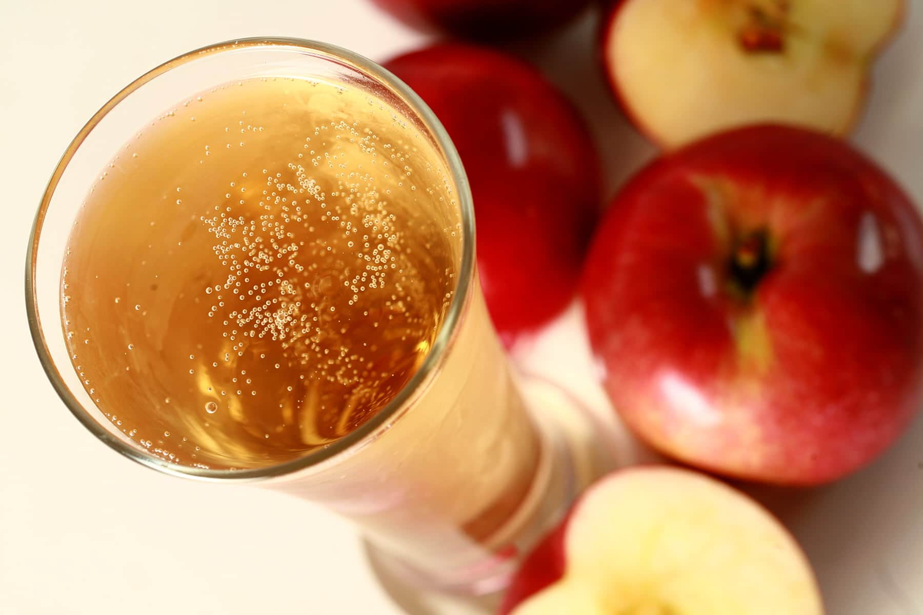 Close of view of a glass of homemade hard apple cider, surrounded by red apples.
