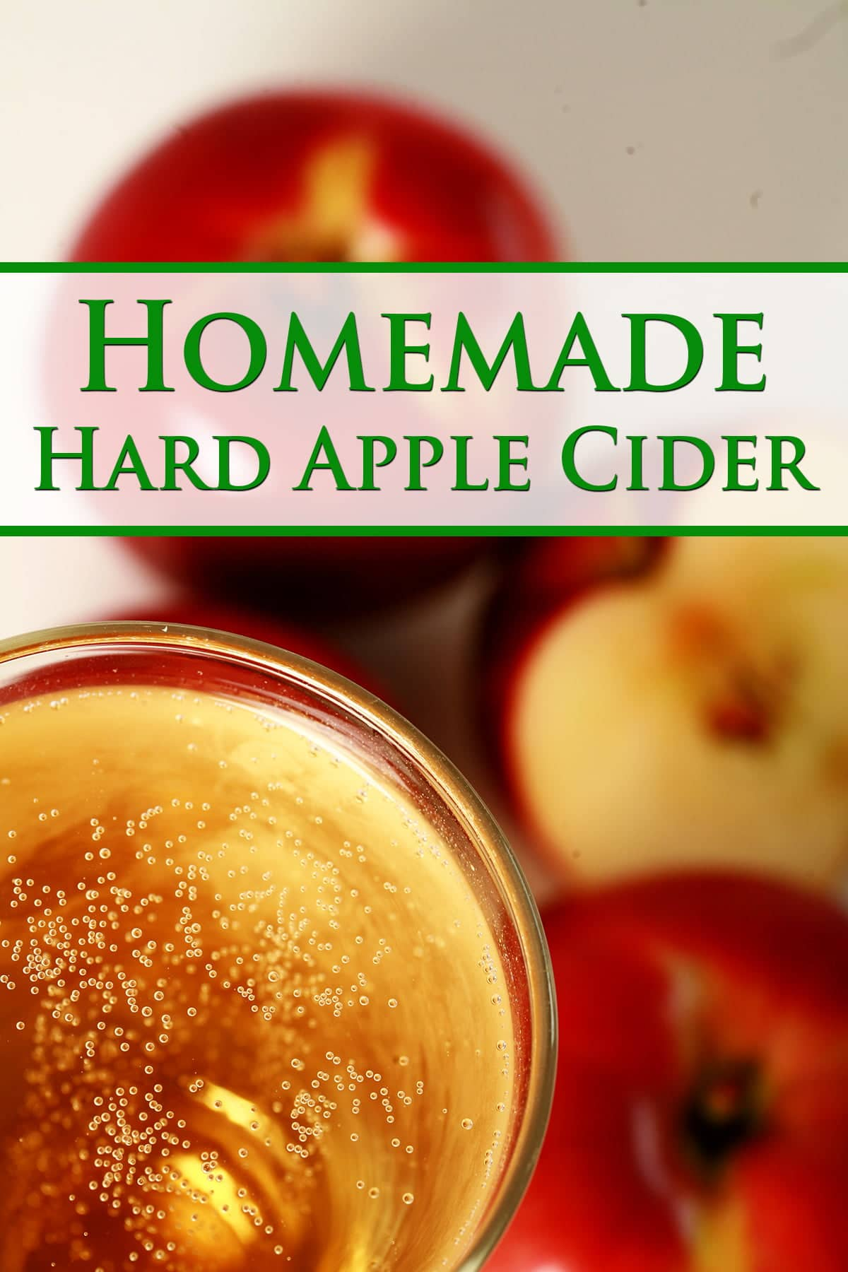 Pinterest image for this Hard Apple Cider recipe.  A close up view of a glass of hard apple cider, with red apples surrounding it.