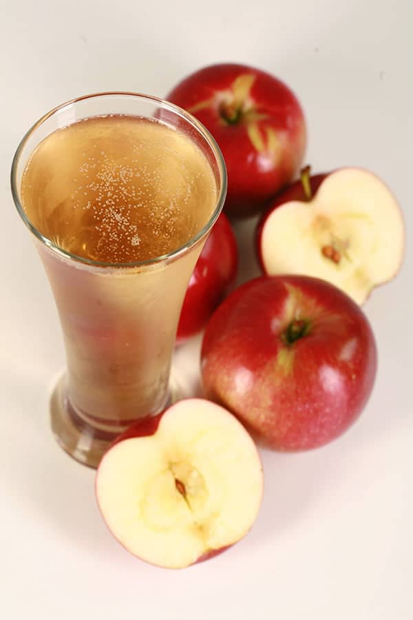 Glass of Homemade hard apple cider with apples surrounding it