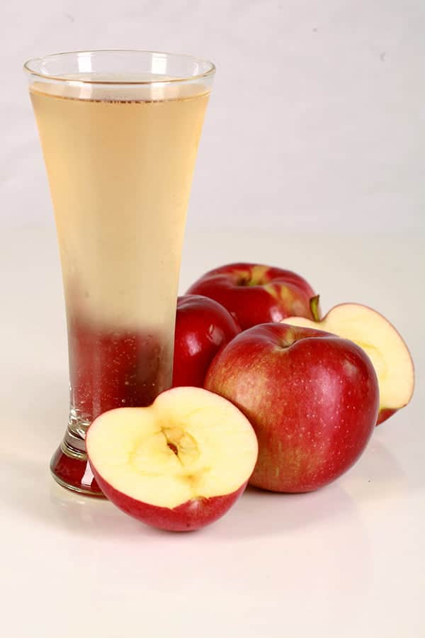 Image of a tall glass of pale gold carbonated cider, with several apples surrounding it