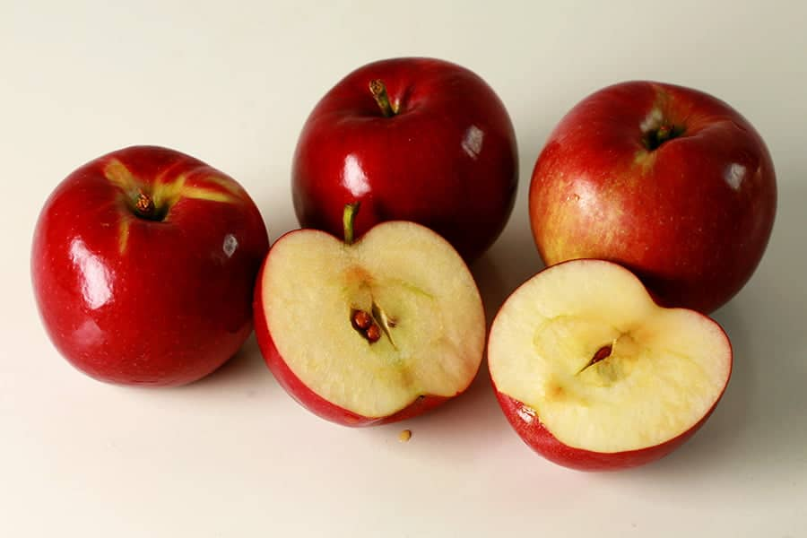 Image of 3 red apples, with a 4th cut in half