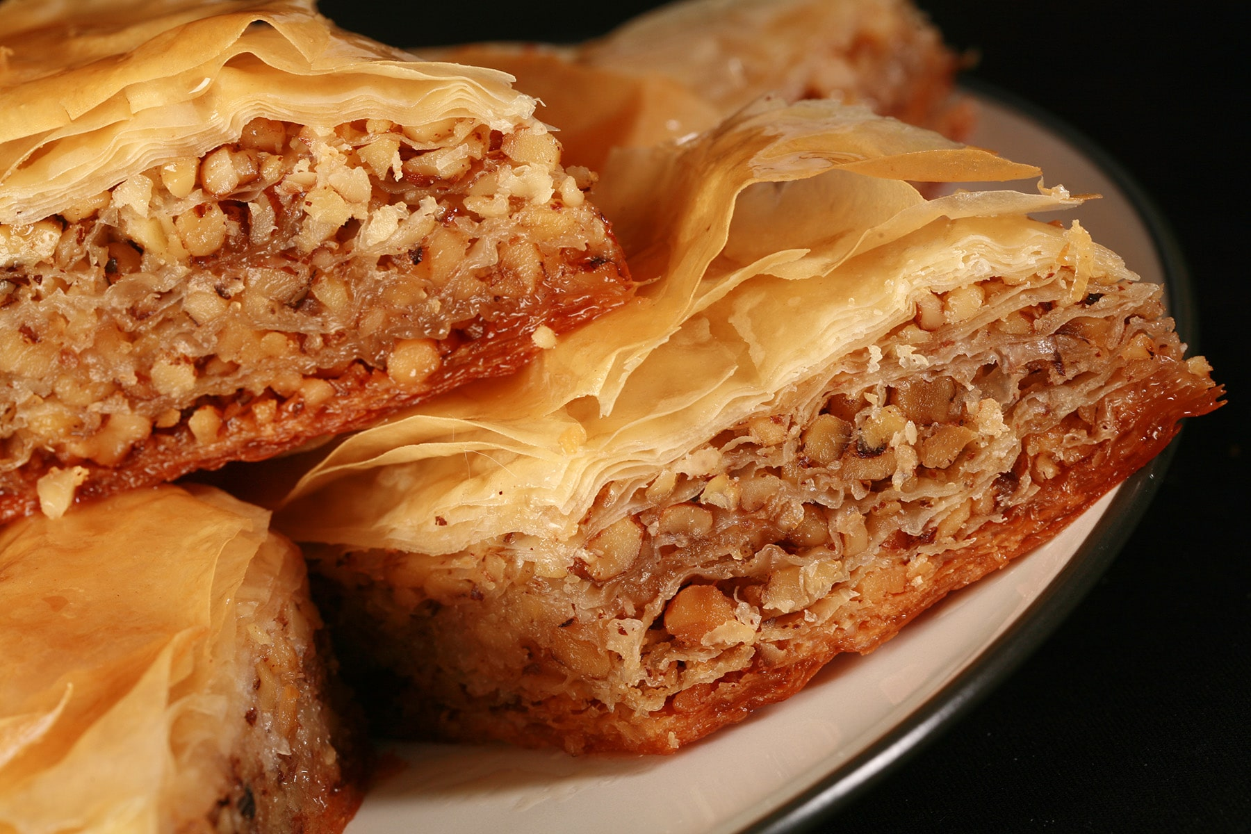 A close up view of a diamond shaped maple walnut baklava on a small white plate.