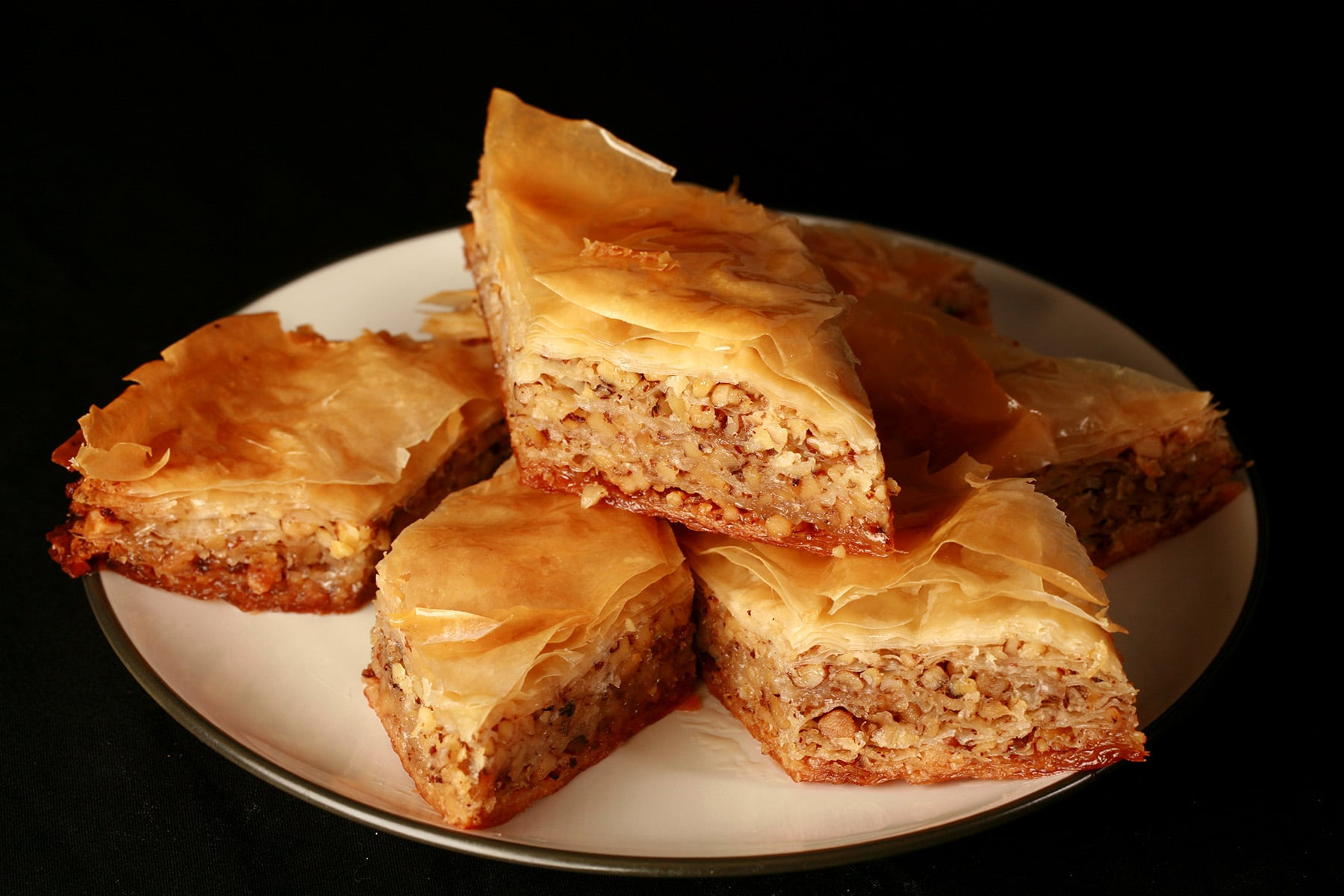 Diamond shaped pieces of maple-walnut baklava, on a small white plate.