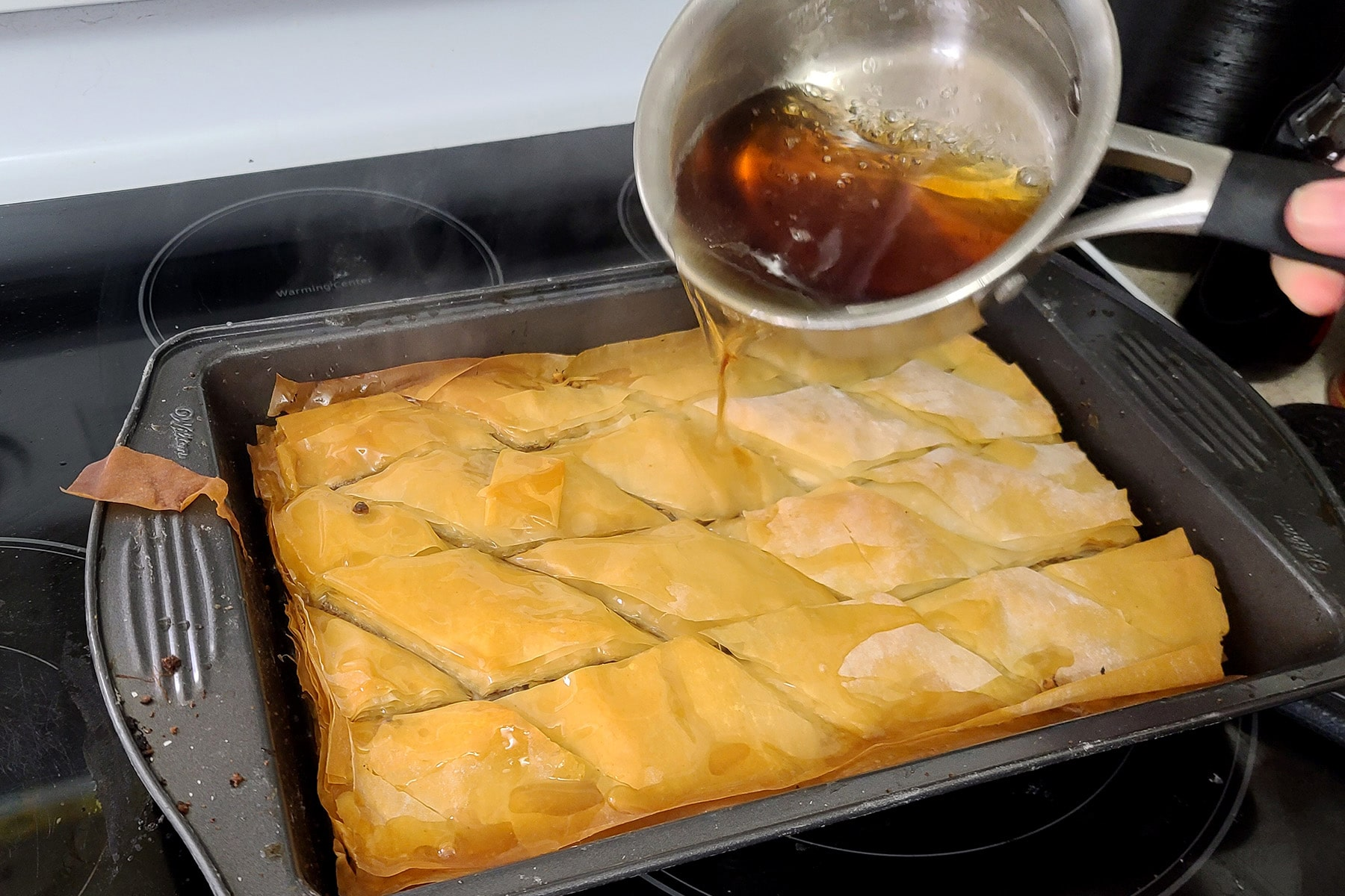 The pot of maple syrup mixture is being poured over the baked pan of baklava.