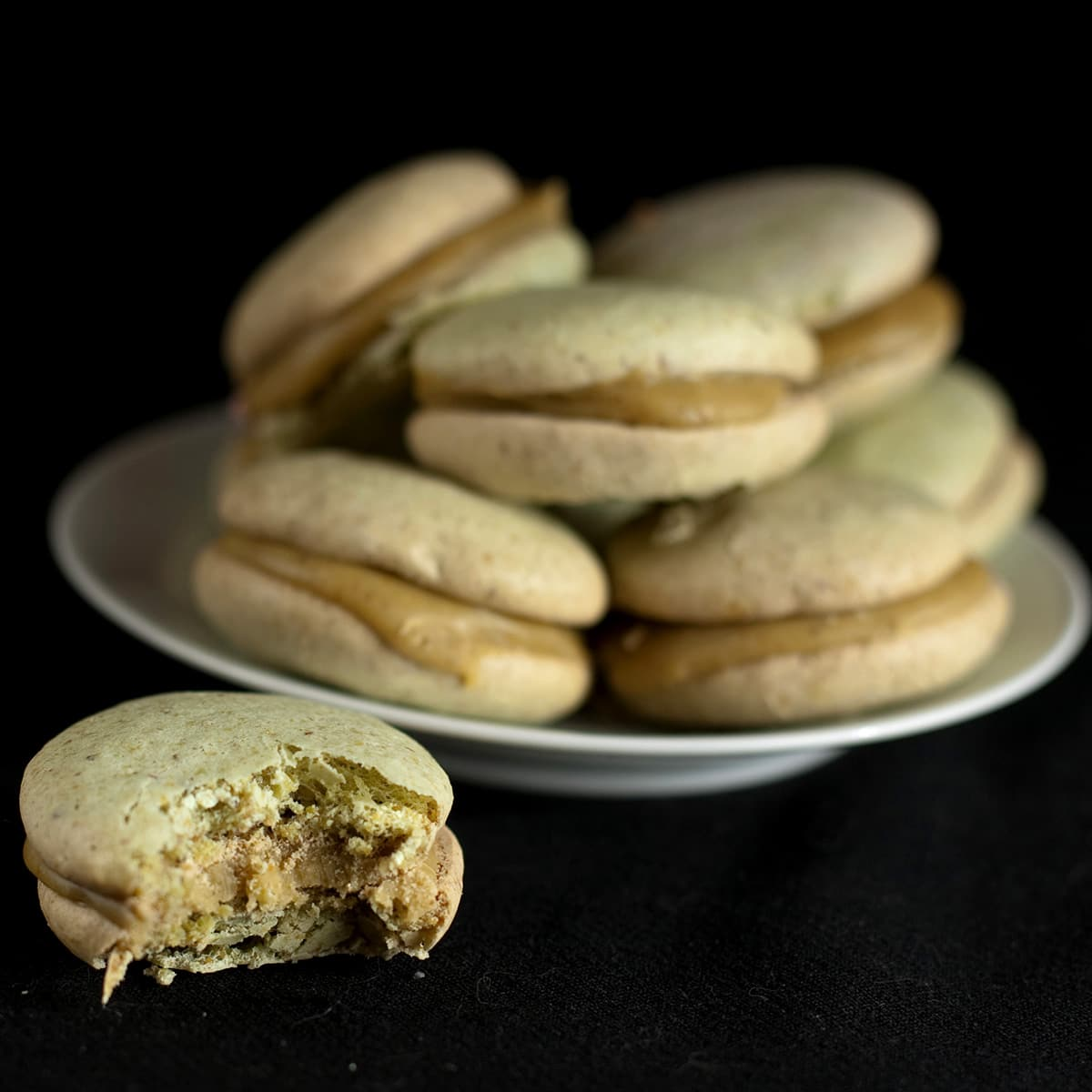 A small white plate with a pile of pistachio macarons on it.