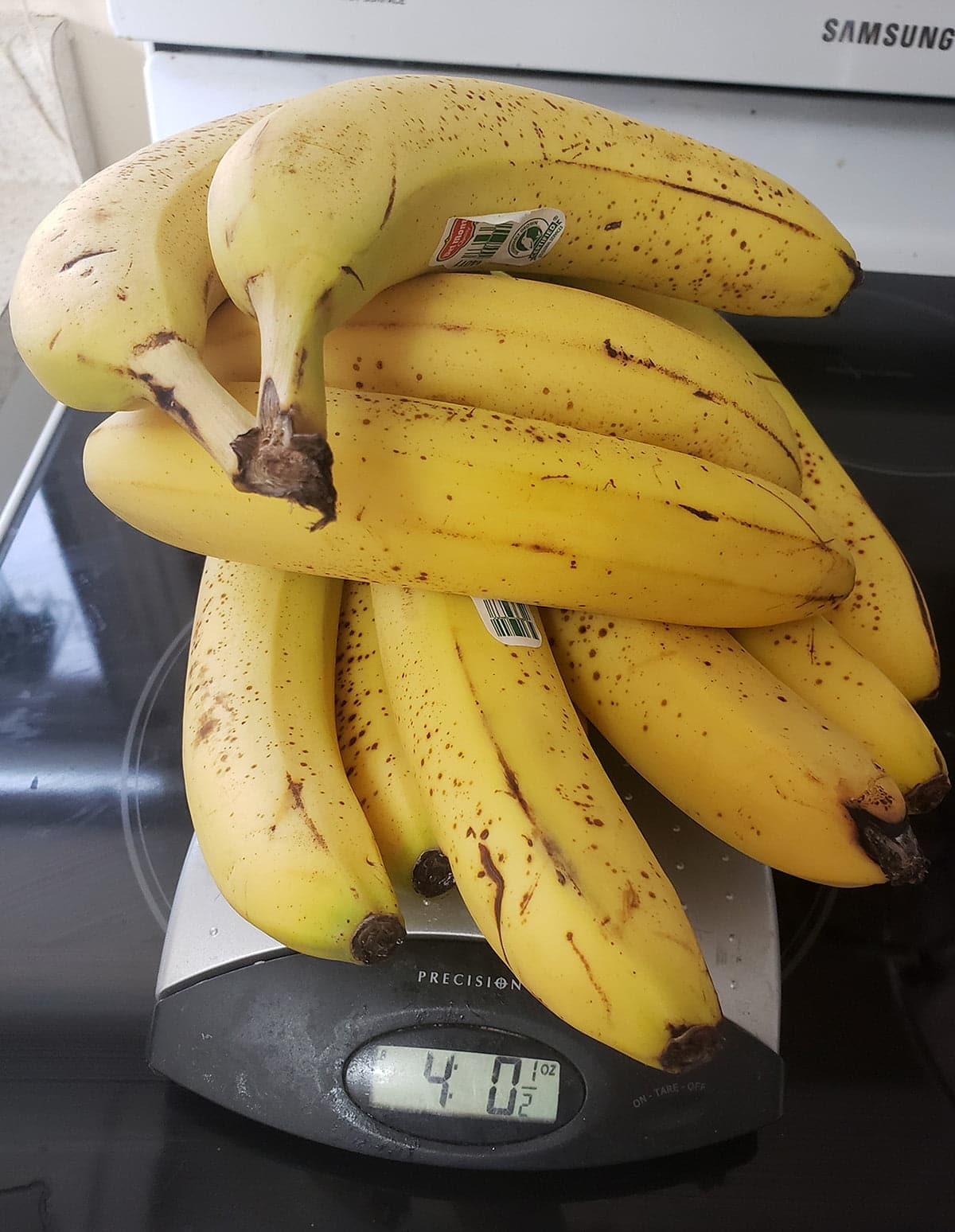 A pile of fresh bananas rests on top of a scale.