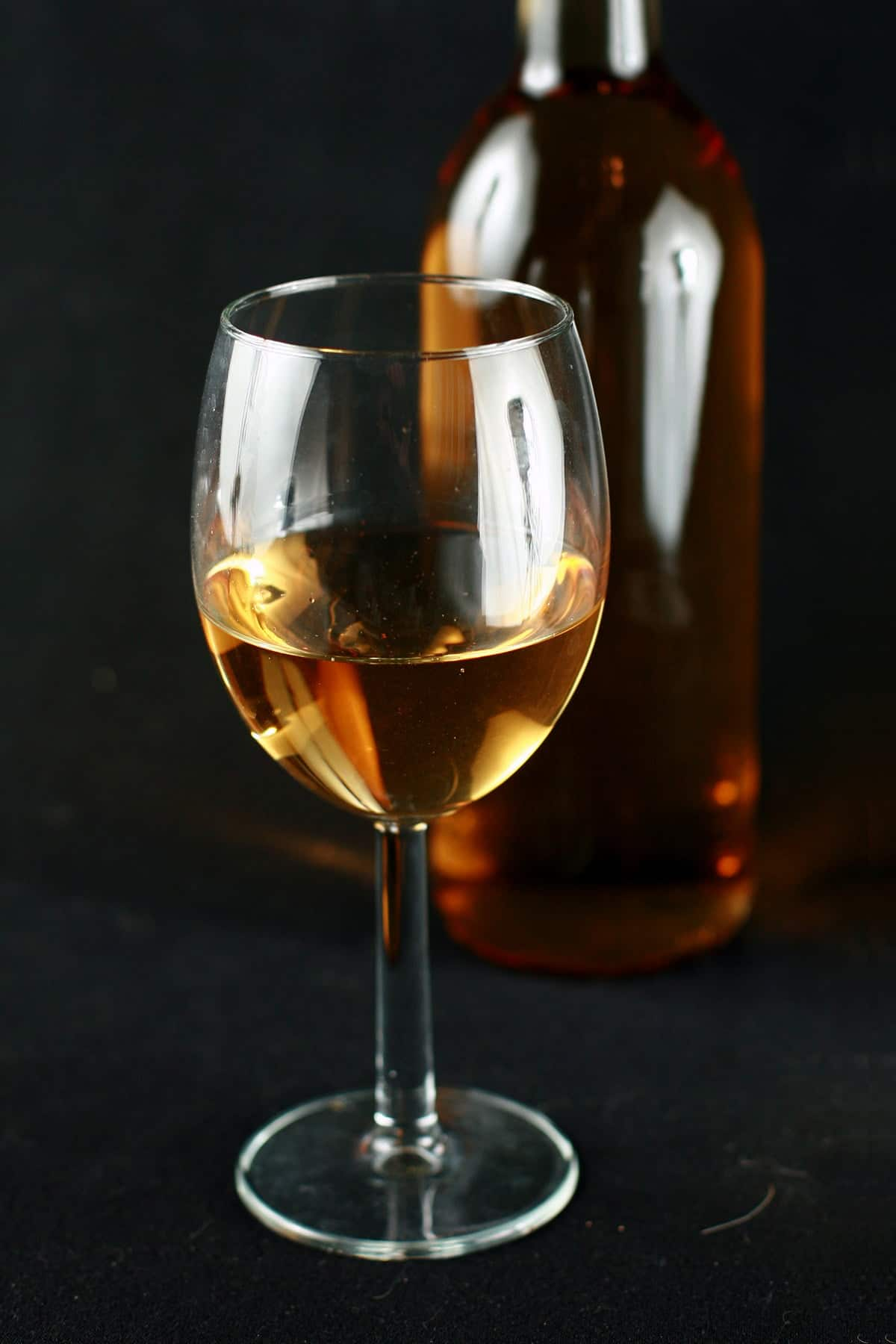 A wine glass and a wine bottle are filled with golden wine, against a black background.