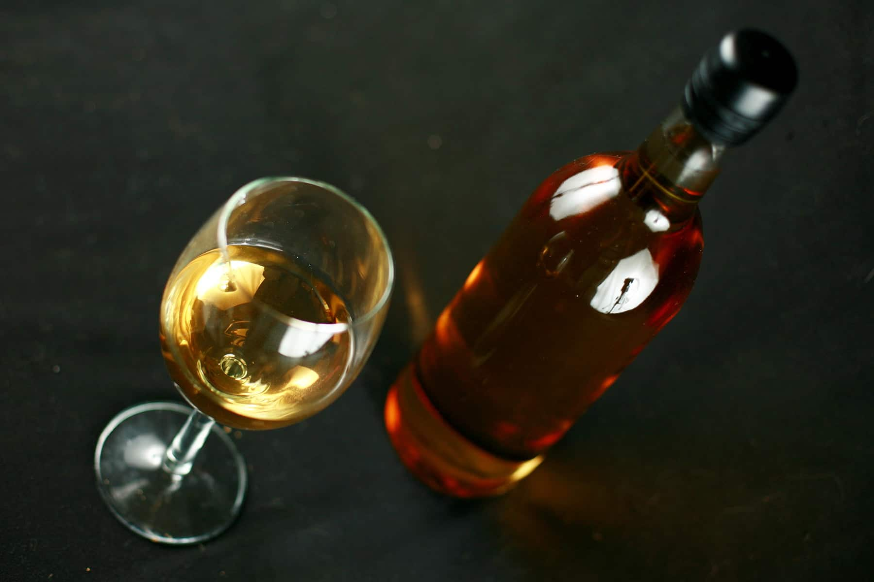 A wine glass and a wine bottle are filled with golden banana wine, against a black background.