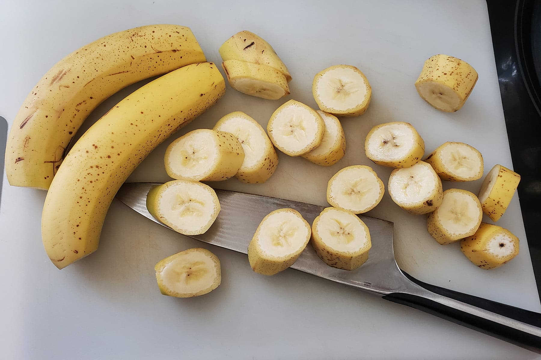Bananas - whole and sliced - scattered across a cutting board.