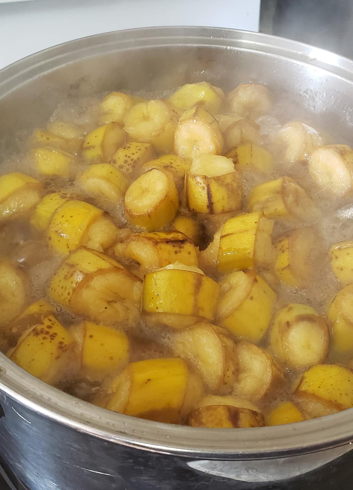 A large pot is full of sliced bananas.  They are puffed up from the cooking processes, and enveloped in steam.