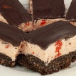 Close up view of a plate of 3 layered bars. The bottom layer looks like a brownie, the middle is a thick pink buttercream with bits of cherry visible, and the top is a smooth chocolate ganache.