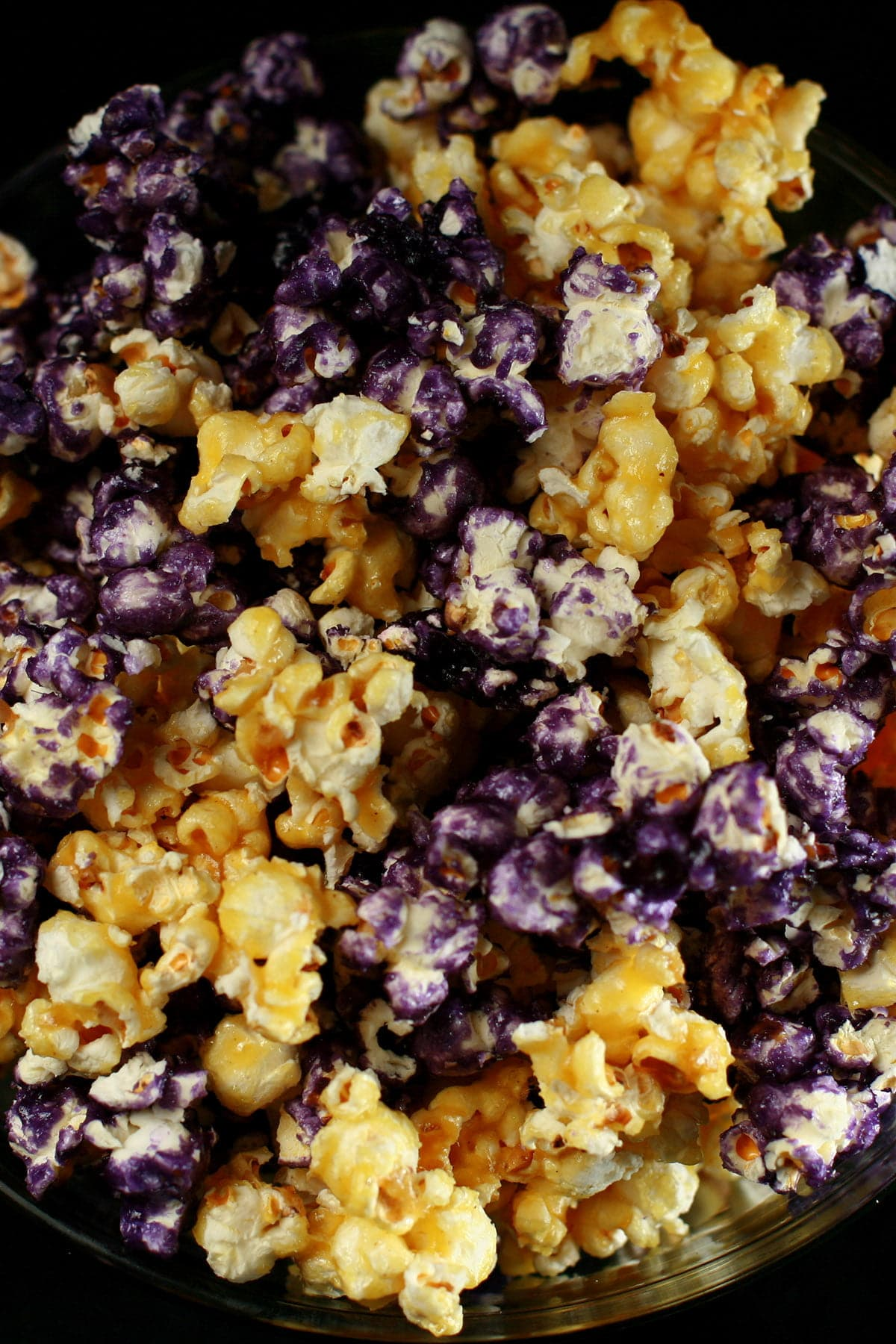 A close up view of yellow and purple glazed popcorn.