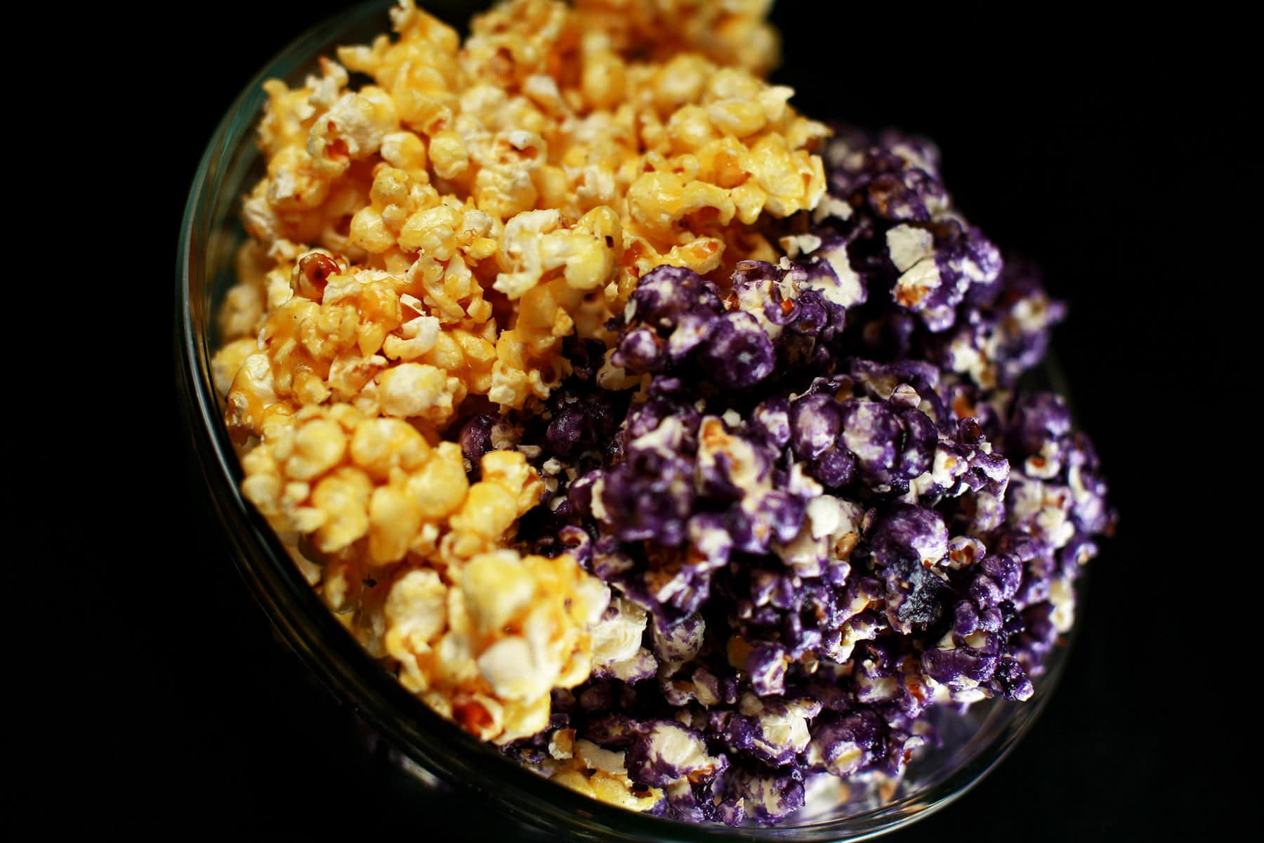 A close up view of yellow and purple fruity glazed popcorn.