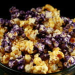 A close up view of a bowl of glazed popcorn. The game day popcorn is yellow and purple, themed around a sports team.