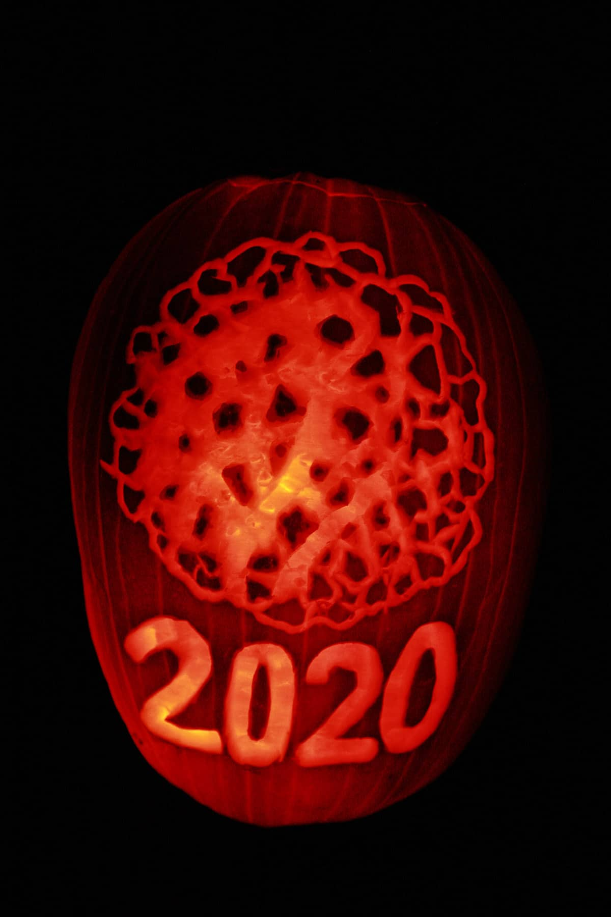 A Halloween pumpkin carved with a coronavirus design and 2020.