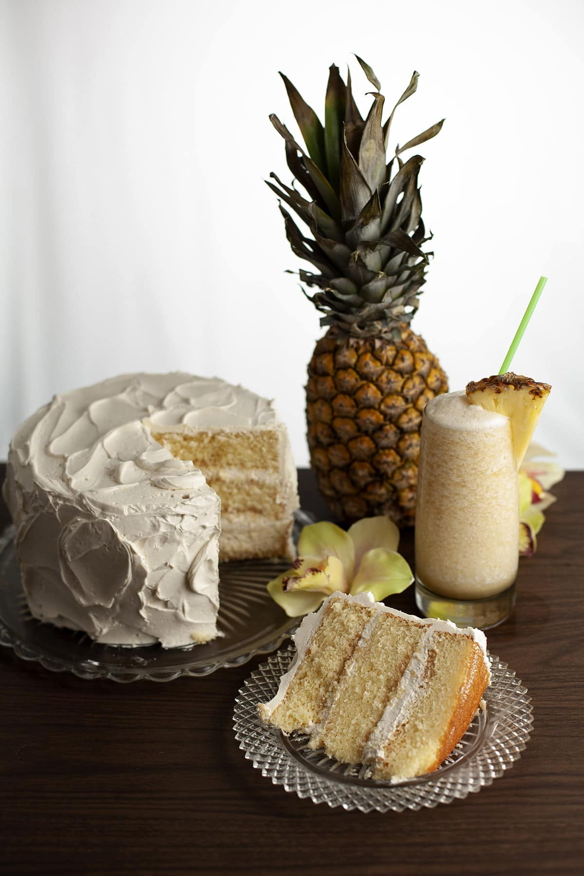A slice of Bahama Mama torte is shown next to the cake it is cut from. 3 layers of a white cake, filled and frosted with a white frosting. A pimeapple, a yellow cymbidium orchid, and a tropical cocktail - a Bahama Mama - are shown next to and behind the cake.
