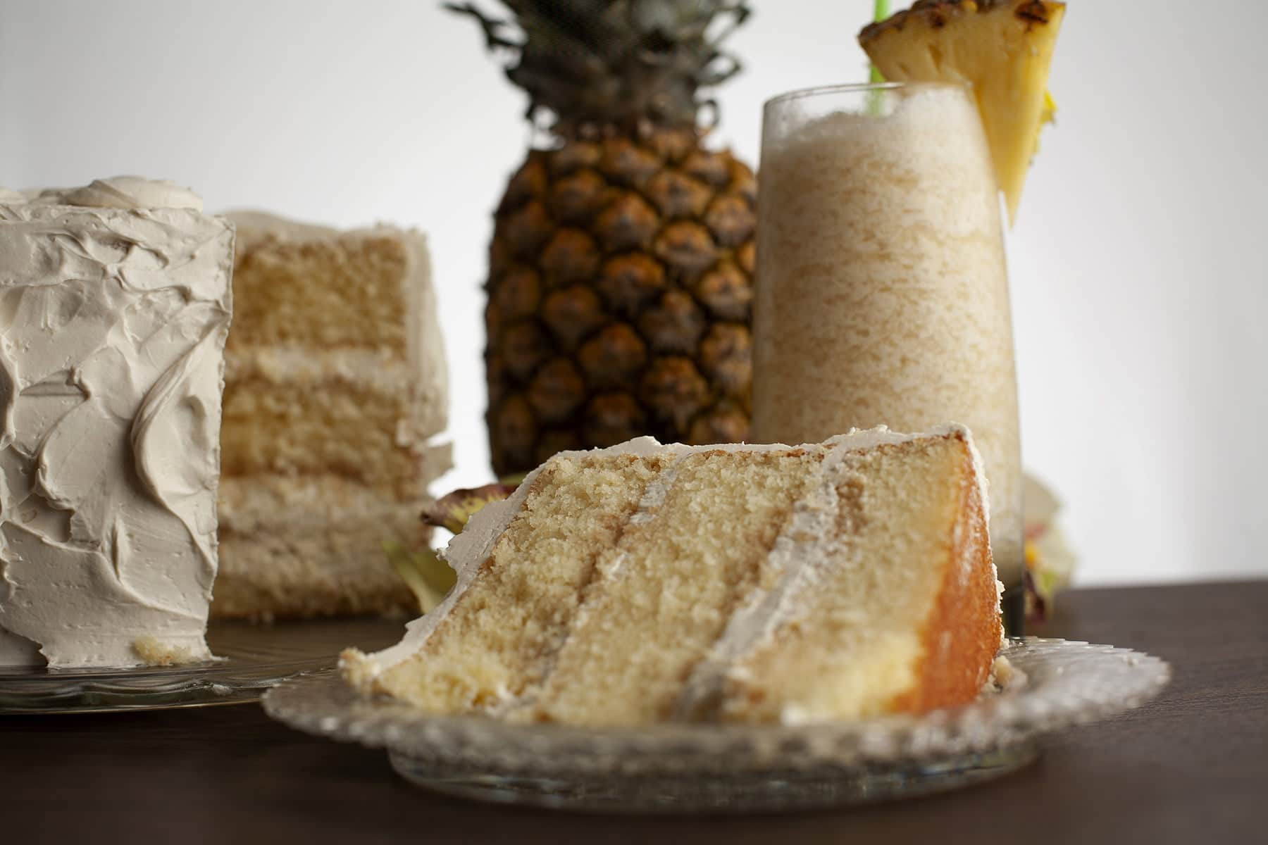 A slice of Bahama Mama cake is shown next to the cake it is cut from. 3 layers of a white cake, filled and frosted with a white frosting. A pimeapple, a yellow cymbidium orchid, and a tropical cocktail - a Bahama Mama - are shown next to and behind the cake.