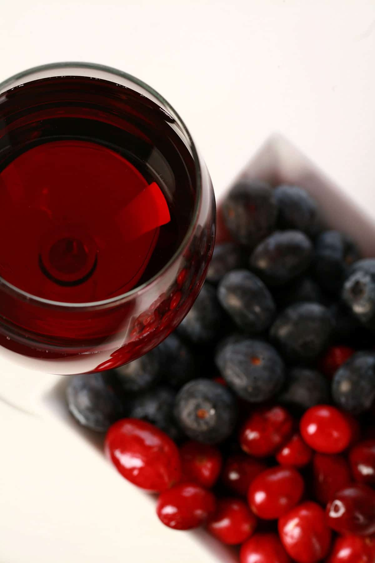 A glass of red wine - made from this faux lingonberry wine recipe - is pictured next to a small bowl of cranberries and blueberries