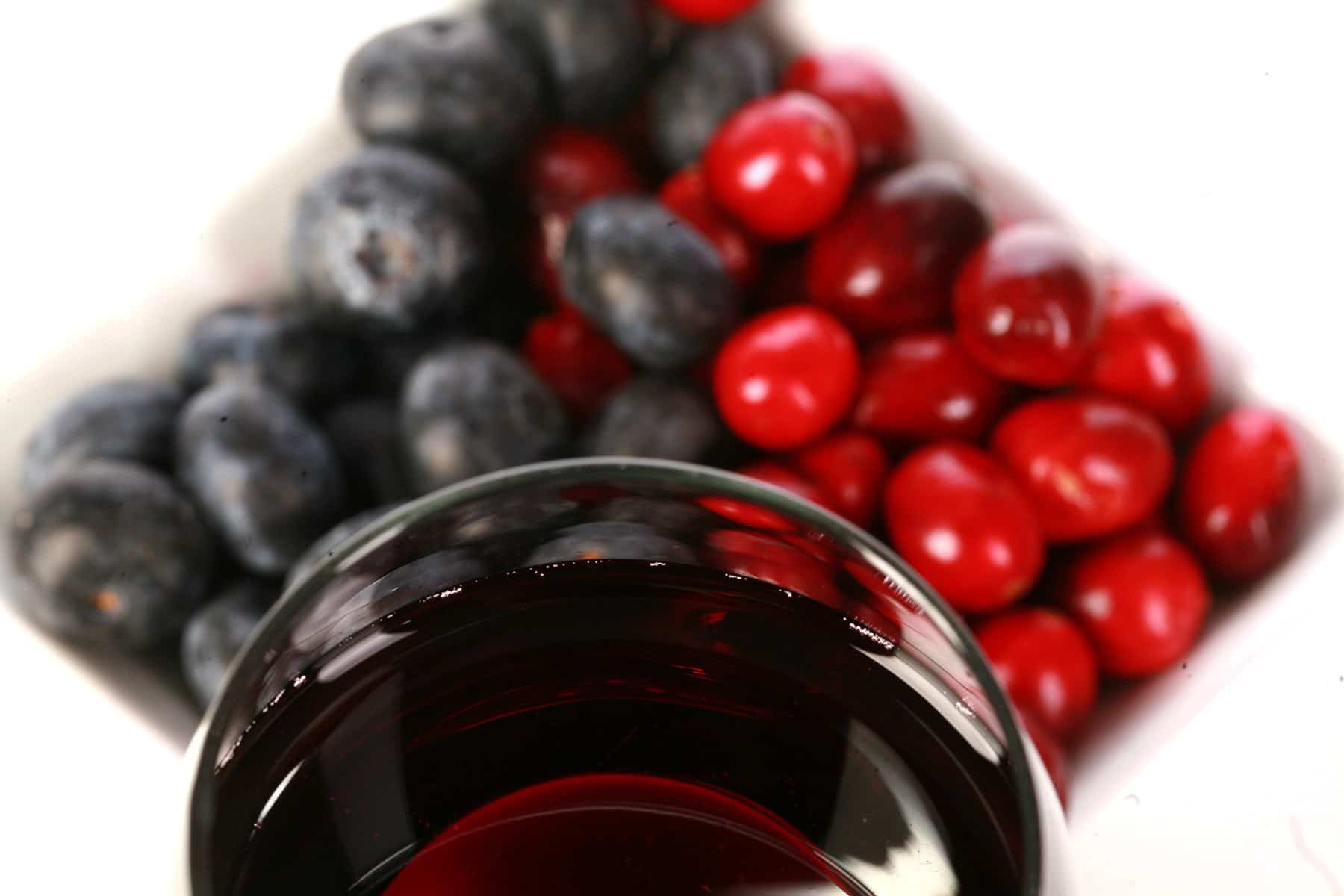 A glass of red wine is pictured next to a small bowl of cranberries and blueberries.