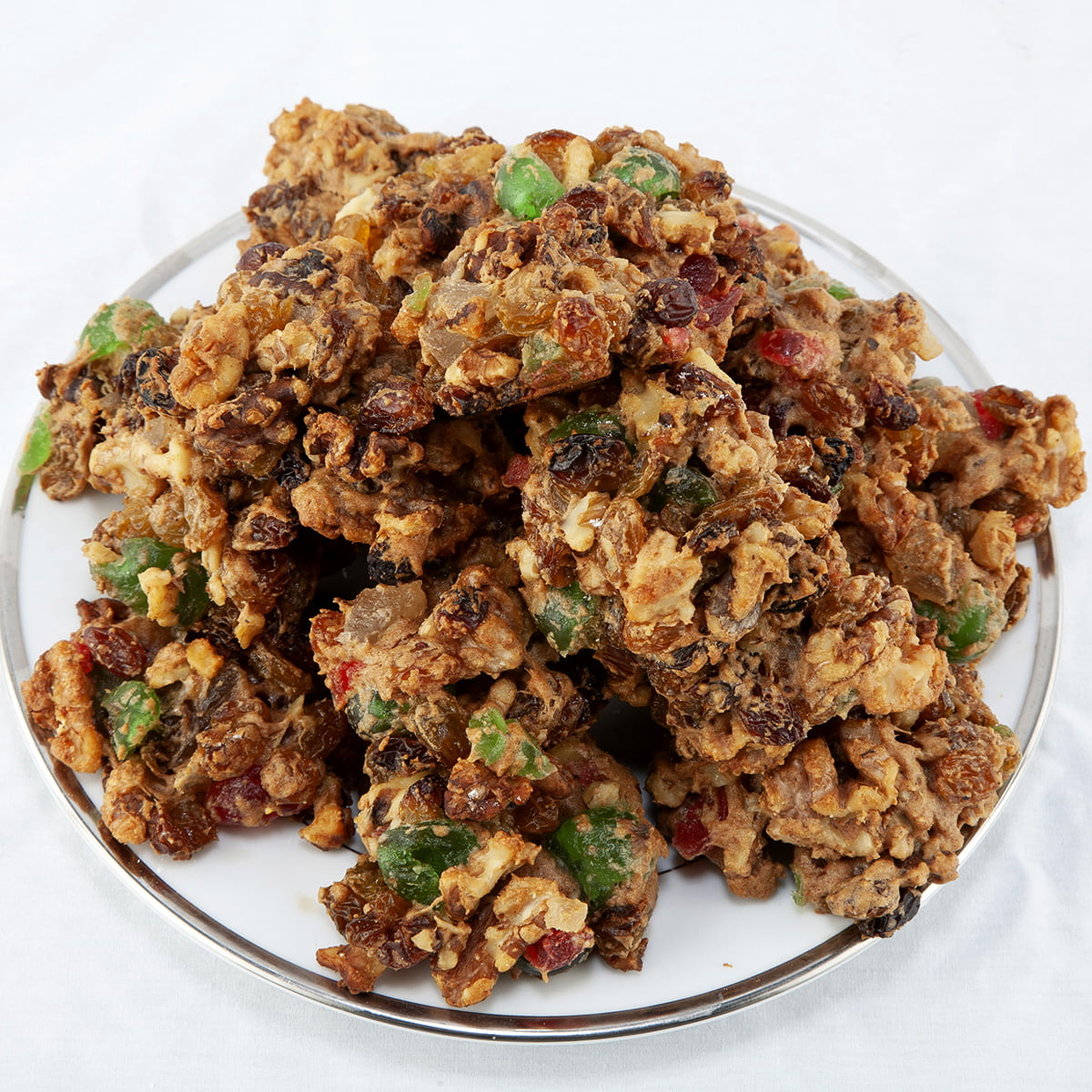 A plate of fruitcake cookies - darkish brown cookies with nuts and chunks of red and green glaceed cherries throughout.