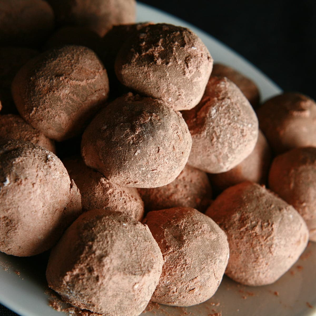 A small plate with a pile of cocoa-coated milk chocolate truffles.