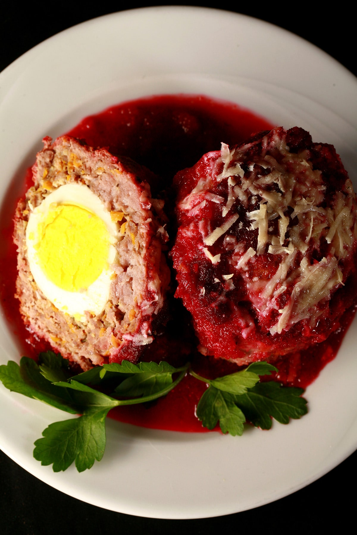 An individual scotch egg meatloaf on a white plate, with a half meatloaf next to it. The half serving shows the hard boiled egg surrounded by meatloaf.
